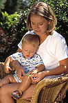 Young mother dressing scratch on her baby son's knee with a brightly colored/coloured plaster