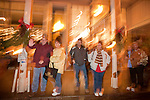 Spectators on the sidewalk watch Sutter Creek's annual Parade of Lights Christmas parade downtown on a rainy night in the  Mother Lode of Calif.