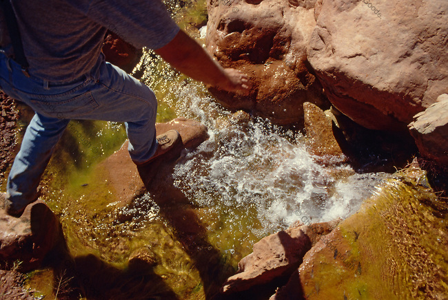 Photograph of a Hiker Stepping across a Stream