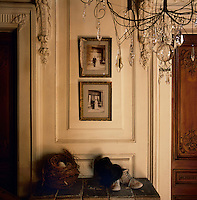 Family wedding photographs are displayed on a panelled wall in a traditional room. A delicate wrought-iron chandelier with glass drops is seen in the foreground.