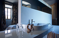 A floating wall separates the bathroom from the sleeping quarters in this modern guest room