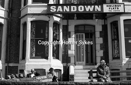 "PEOPLE ON HOLIDAY IN BLACKPOOL, ENJOY THE SUNSHINE SITTING OUTSIDE THEIR HOLIDAY FLATS OVER LOOKING THE ""GOLDEN MILE "" 1970S UK"