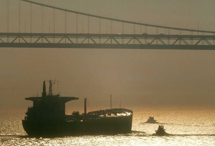California, Oil, Super tanker, San Francisco, tugs move to assist tanker beneath the Bay Bridge, San Francisco Bay, Heavy smog, This image was taken on 1980 at a time that smog in US was at its worst..