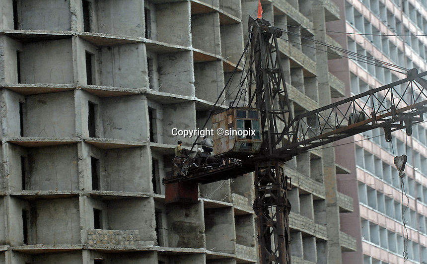 Construction of another concrete eatern european-style throw-back tower block in PyongYang, North Korea.