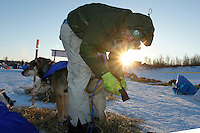 Rookie musher Kelly Maixner boots his team as he prepares to leave the ghost-town checkpoint of Iditarod as the sun rises on Friday morning during the 2011 Iditarod race..