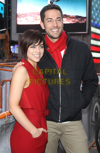 Zachary Levi and Krysta Rodriguez and the cast of Broadway's First Date ring the NASDAQ closing bell at Times Square in New York City, NY., USA.<br /> October 16th, 2013 <br /> half length red top scarf white black jacket stubble facial hair jumpsuit side<br /> CAP/MPI/RW<br /> &copy;RW/ MediaPunch/Capital Pictures