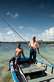 MAURITIUS, Trou D'eau Deuce, fisherman Rolau Dardenne 80 and his grandson Kelvin Dardenne in their boat, preparing to go fishing off of the East coast of Mauritius, Indian Ocean, 4 Sisters Mountain in the distance