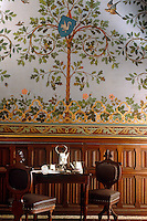 A small table is laid for tea beneath a hand-painted wall depicting a tree with the family crest, flowers and birds