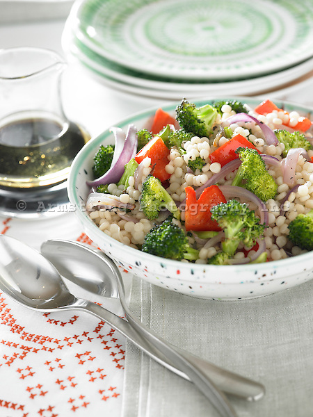 Couscous with red onion, red pepper, and broccoli, with salad dressing on the side