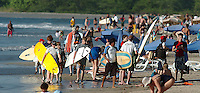 Tourists massing on the main beach in Tamarindo Costa Rica. Some ready to surf, others just ready to sun bathe