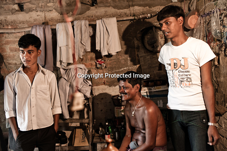 The first ever graduate from the Chowduli class, Siraj Gazi (right) is seen with his younger brother, 18 year old Sahajan Gazi (left) and his father, Jamshed Gazi inside their house in Chaymalpur village of North 24 Parganas in West Bengal, India. Photo: Sanjit Das/Panos for The Wall Street Journal. Slug: ICASTE