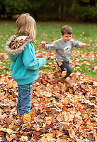 Boy running in fall leaves wile girl is watching