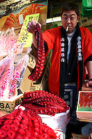 Octopus Vendor at Ameyoko Market, Tokyo.  Ameyoko or Ameyocho as it is sometimes called was once Tokyo's black market district.  Nowadays it is given over to selling knockoff designer jeans, sunglasses, bulk food items, fish and just about anything you can think of.  It is liveliest at night with spillover passengers from nearby Ueno Station.