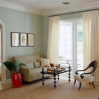 A cool corner of the living room with a grey linen-covered sofa and an antique armchair arranged next to some French windows hung with white linen curtains