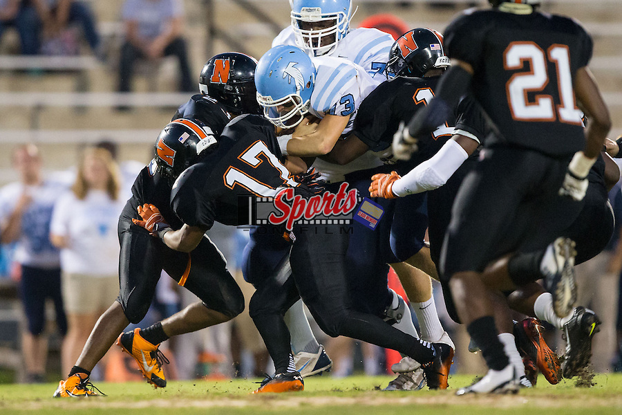 Harrison Baucom (13) of the West Rowan Falcons is hit by a host of Northwest Cabarrus Trojans defenders during first half action at Trojan Stadium September 19, 2014, in Concord, North Carolina.  The Falcons defeated the Trojans 13-0.  (Brian Westerholt/Sports On Film)