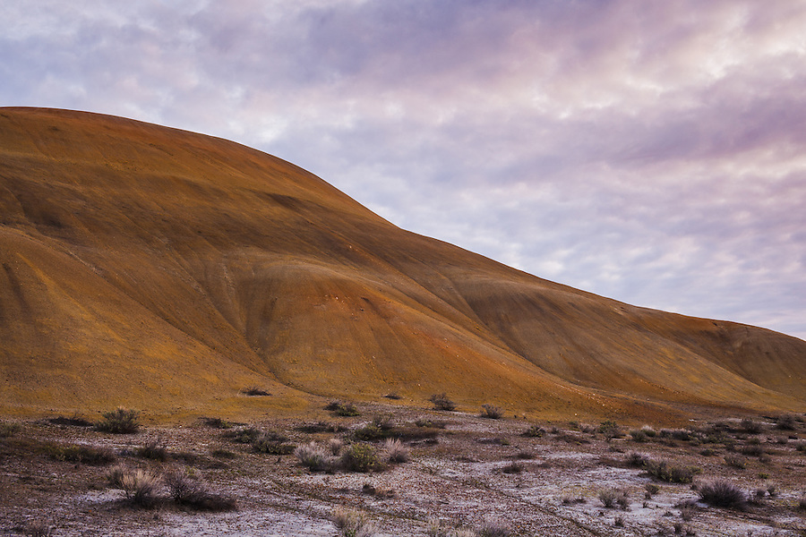 Orange colored hills are seen under a partly cloudy sky in the Painted Hills section of the John Day fossil beds national monument in Wheeler County, Oregon.