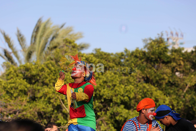A Palestinian man dressed as a clown takes part during a cultural carnival organized by Gaza Municipality in Gaza City April 1, 2016. Photo by Mohammed Asad