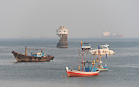 Old and new boats surround Dolphin Rock Lighthouse in Mumbai, India.