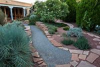 Gravel path between flagstone garden walls in backyard New Mexico garden, design by Judith Phillips