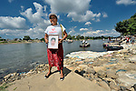 Carmen Lucia Cuaresma, a Nicaraguan woman, holds a photo of her son Alvaro Enrique Guadamuz during a December 18, 2013 demonstration on the banks of the Suchiate River where it forms the border between Guatemala and Mexico. The woman crossed the river from Mexico to join in a demonstration in Tecun Uman, Guatemala.<br /> <br /> Cuaresma came to the area as part of a caravan of 45 people from Central America who spent 17 days touring 14 Mexican states in search of their loved ones, most of whom had disappeared while following the migrant trail north. In addition to searching for clues to the fate of their loved ones, they called on the Mexican government to improve its treatment of migrants transiting the country.<br /> <br /> Cuaresma last heard from her son in 2011 when he called her from Mexico.