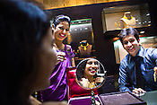 Store assistants admire and share a light moment with a young woman while she tries on gold jewelry at a Mehrasons Jewellers store in New Delhi, India. Photo: Sanjit Das/Panos Pictures
