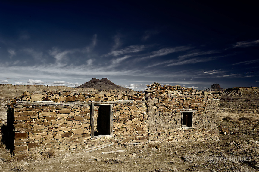 An abandoned adobe and stone ruin in the Rio Puerco Valley of north-central New Mexico. Cabezon Peak and Cerro Cuate are in the background.