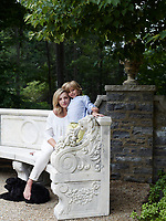 A portrait of interior designer Emma Pilkington with her child in the garden.