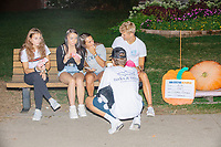 A group of Des Moines high school students gather near champion pumpkins at the Iowa State Fair in Des, Moines, Iowa, on Sun., Aug. 11, 2019.