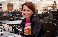 Attractive woman in city center having beer at outdoor cafe, Lviv Ukraine