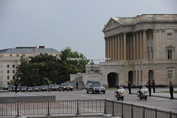 """The hearse carrying the body of former U.S. Senator Edward """"Teddy"""" Kennedy trailed by a motorcade with members of the Kennedy family stops briefly for prayer and remembrance en route to Arlington National Cemetery in front of the U.S. Senate in Washington, D.C. on August 29, 2009."""