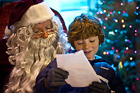 Christopher Givens reads to Santa from his two-page gift list. Givens was one of more than 100 children who sat on Santa's knee to deliver their requests for toys on Christmas morning after Santa's arrival at the Christmas Tree lighting ceremony. Givens is one of the few who brought a written list and the only one with two pages.