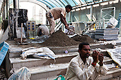 A construction worker checks his mobile phone, while others are seen working on the pavement outside the Jawahar Lal Nehru metro station in New Delhi, India.