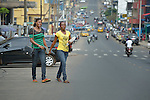 Isabella Washington (left), 26, and Catherine Hill, 28, walk across a street in Monrovia, Liberia, after attending class at United Methodist University. Both women are studying with help from scholarships from United Methodist Women.