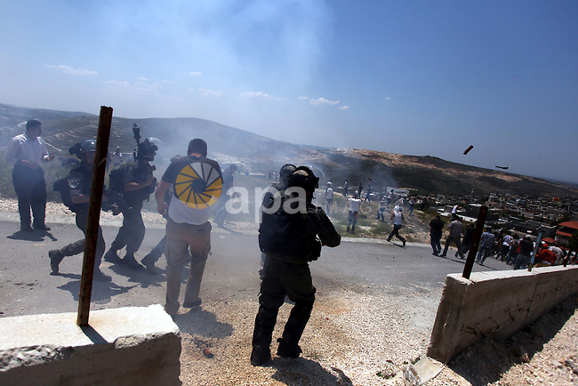 An Israeli Border officer fires tear gas at Palestinian villagers during clashes with Jewish settlers in Oref village near Nablus City 30 April 2013. Reports state that the clashes occured after an Israeli settler was stabbed to death by a Palestinian man. Israeli media reported that the Palestinian attacker took the settlers' weapon and began firing at a nearby Israeli border guard force, who returned fire, wounding the attacker. Photo by Issam Rimawi