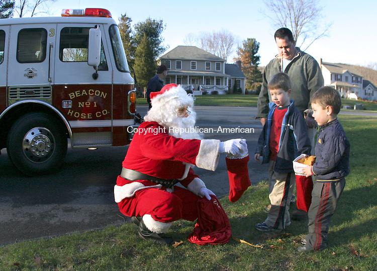 BEACON FALLS, CT- 16 DECEMBER 2006- 121606JW02.jpg  -- Santa Claus brings gifts to Brendan Rowley of Beacon Falls and his sons Brendan Rowley age 7 and Andrew Rowley age 4 Saturday afternoon. Santa rode around town in Beacon Hose Co. #1 Engine 3 Saturday distributing gifts.  Jonathan Wilcox Republican-American