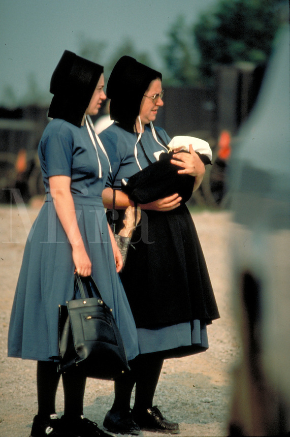 An Amish mother holds baby as she walks with an adult female relative. They wear large bonnets and Amish dress. Amish women. Kidron Ohio United States.