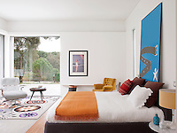 A contemporary, white bedroom with a full height window. A white leather Eames recliner stands on a vibrant carpet entitled Stela by Carpet Diem.  A Hermes orange blanket is draped at the foot of the double bed.