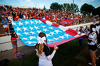 Omaha Burke High School cheerleaders roll out a handmade flag for the national anthem during the Omaha Burke vs. Westside football game at Burke High School in Omaha, Nebraska.
