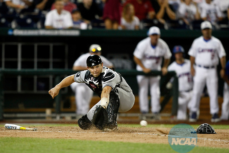 27 JUNE 2011:  Catcher Robert Beary (4) of the University of South Carolina scoops a ball out of the dirt for a force out against the University of Florida during the Division I Men's Baseball Championship held at TD Ameritrade Stadium in Omaha, NE.  South Carolina defeated Florida 2-1 to win Game 1 of the championship series.  Jamie Schwaberow/NCAA Photos
