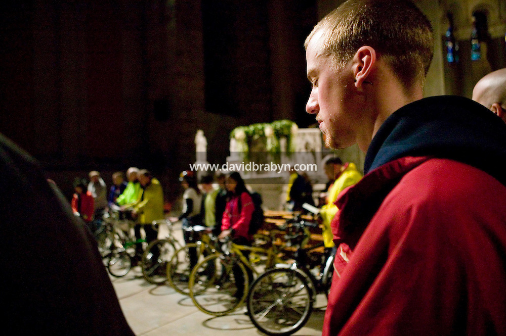 22 April 2006 - New York City, NY - Cyclists pray during the annual blessing of the bicycles at the Cathedral of St John the Divine in New York City, USA, 22 April 2006. Several dozens cyclists, professional and recreational, and a few roller skaters attended the ceremony  during which prayers are said for those who died in cycling accidents this year and for a safe season. Photo Credit: David Brabyn