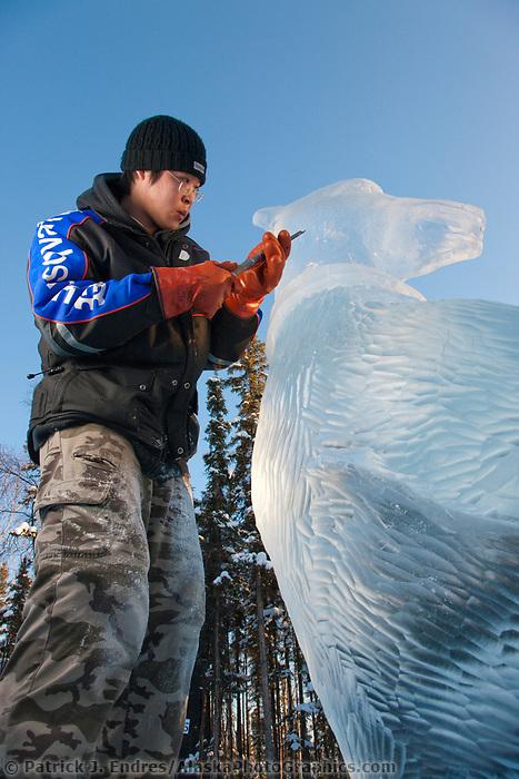 "2009 World Ice Art championships, Fairbanks, Alaska. Multi-block sculpture competition. Realistic category, titled ""50th Celebration of Sourdough Band"" by Chinese sculptors: An, Di; An,Qi Feng; Mu,Qun Li; An, Zhe. An Di applies texture patterns to the bear."