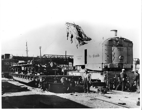D&amp;RGW steam derrick #024 on track beside flat car loaded with various pieces of railroad equipment.  Several workmen are standing by.<br /> D&amp;RGW  Pueblo, CO  ca 1950