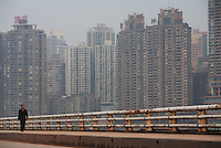 A man walks down a road with the buildings of downtown in the background in Chongqing, China..16 Oct 2007