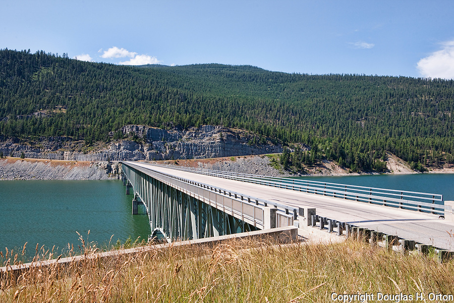 "Koocanusa Bridge, the longest and highest in Montana.  Scenic Lake Koocanusa lies north of Libby, Montana and is formed by Libby Dam, blocking the Kootenai River and forming a resevoir nearly four hundred feet deep and fourty-eight miles long.  Scenic drives encircle the lake crossing over at the ""long bridge"", Montana's longest span."