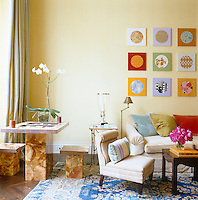 A corner of the living room is furnished with an onyx backgammon table and a pair of matching stools next to a beige velvet sofa with cushions chosen to co-ordinate with a series of small paintings on the wall