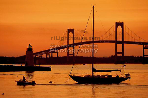 A beautiful orange sunset with a beautiful view of the Newport Bridge and Goat Island Lighthouse
