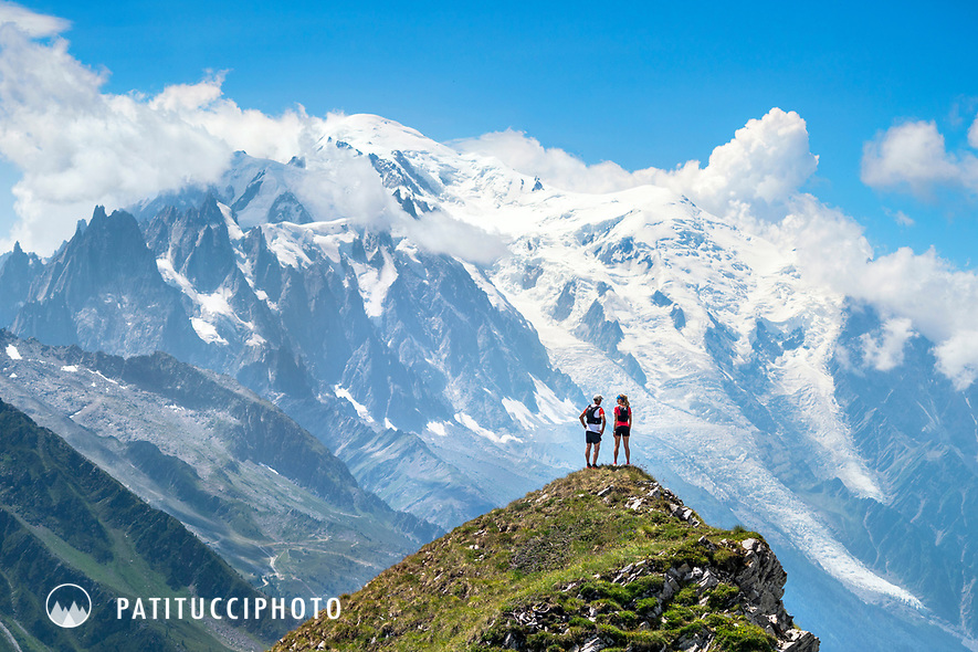 A couple looking out at Mont Blanc from the Col de Balme, on the Swiss French border, above Trient, Switzerland.