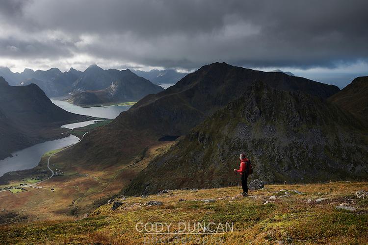 Female hiker on trail towards summit of Stornappstind (740m), Flakstadøy, Lofoten Islands, Norway