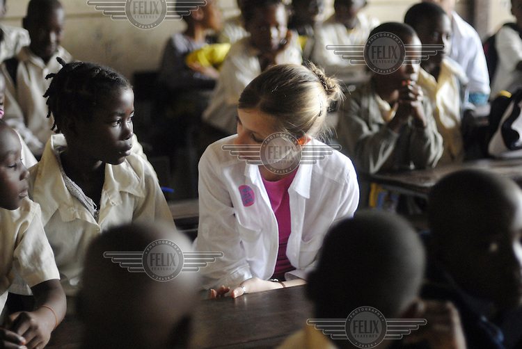 British student education campaigner Lilly King Taylor (C) talks to students in a classroom at Forces Primary School during the 'Every child needs a teacher' campaign.  She is visiting Mozambique as part of a cultural exchange to urge political leaders to provide education for all children in developing countries..