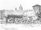 Fireman's-side view of a wrecked engine without a cab.  In the background is a water tank and a board-and-batten building.  This is the same engine as shown in RD094-006.<br /> D&amp;RG (?)